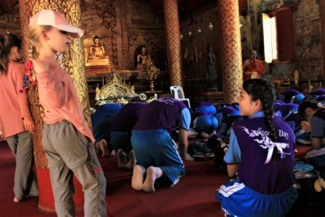 A local schoolgirl looks up from her lesson from the resident monks to make a new friend